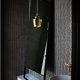 Badrumsinspiration - Liten toalett med svart knappmosaik, stående spegel och mässinglampa av Alvar Aalto för Artek