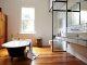 Badrumsinspiration - Vitt 10x20 kakel med svart fog, kaklad hylla, kakellist, badrumslampor på spegel och svart tassbadkar i badrum med teakgolv i Australien